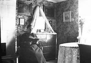 Svartvit interiörbild från förra seklet, med en kvinna som sitter och läser.