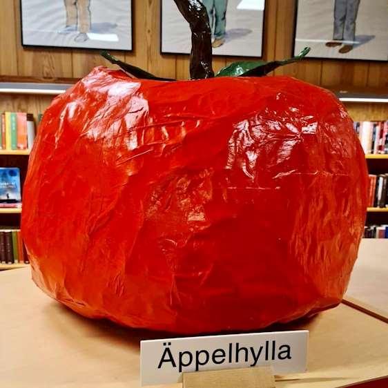 Jättestort rödlackerat äpple står på en bokhylla med skylten Äppelhylla framför.