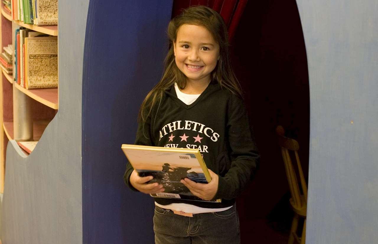 Glad flicka håller i en bok.