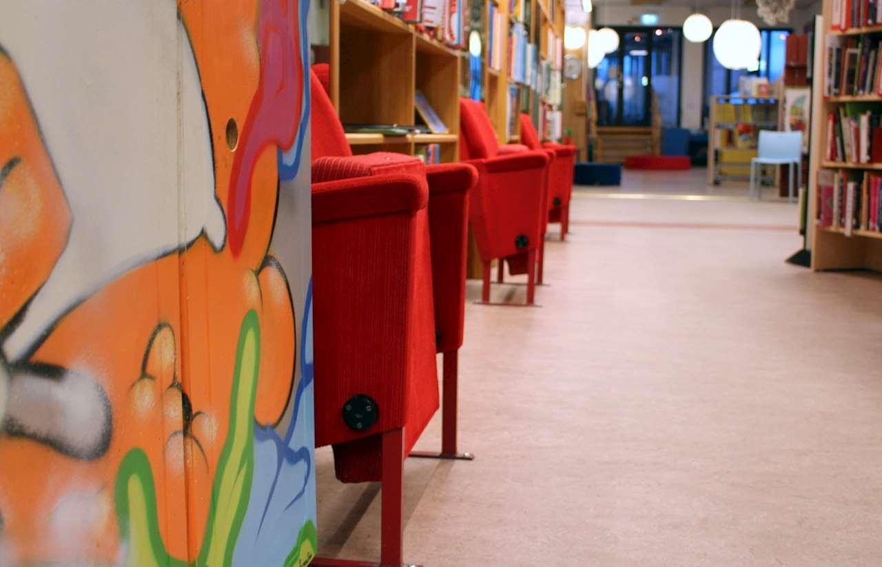 Biostolar och bokhyllor i en rad efter väggen.