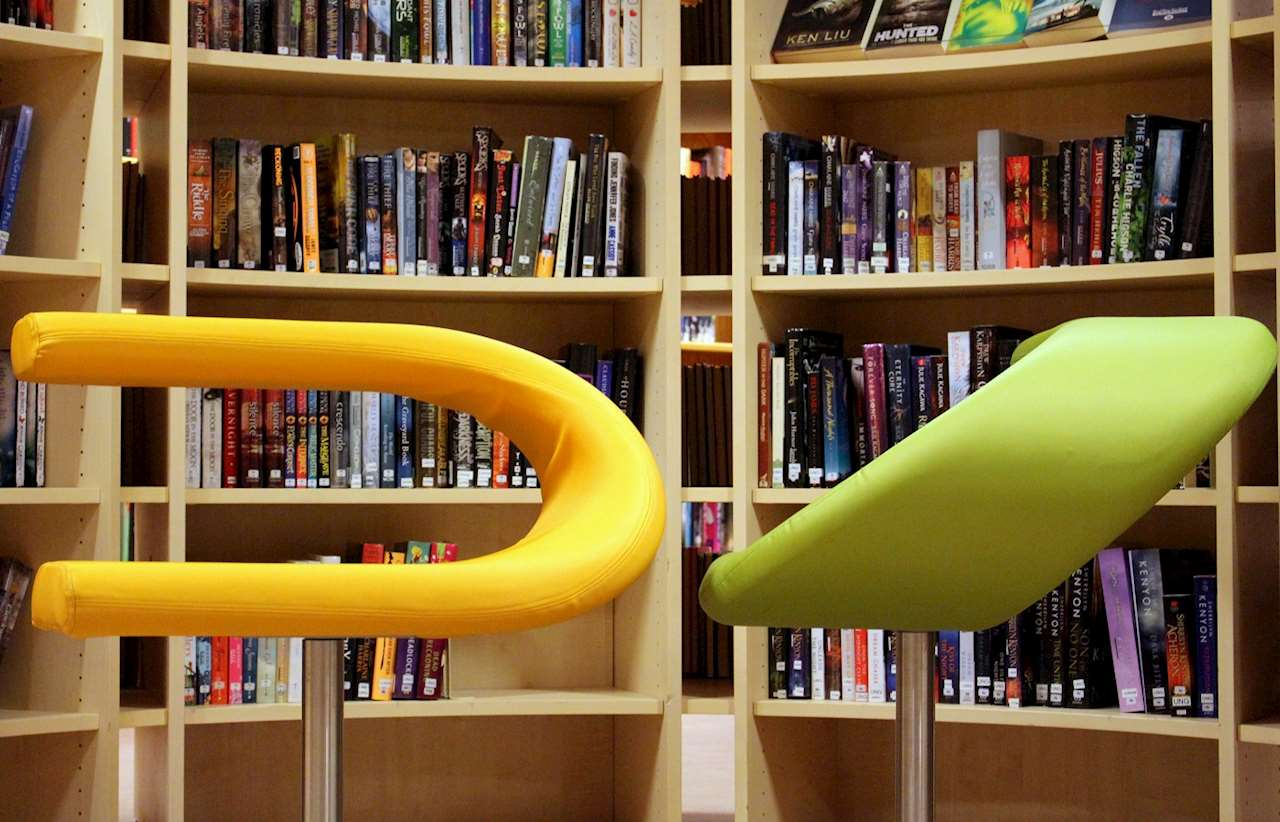 En gul och en grön stol framför en bokhylla.