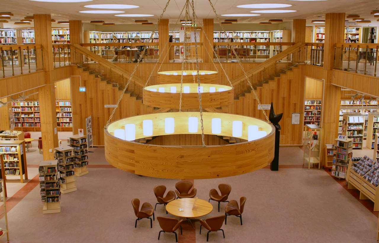 Bibliotekets stora ljushall med högt i tak och stora lampor. Mitt i rummet finns ett antal bord med stolar.
