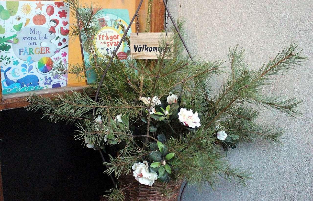 Korg med grankvistar och blommor samt skylt med välkommen.