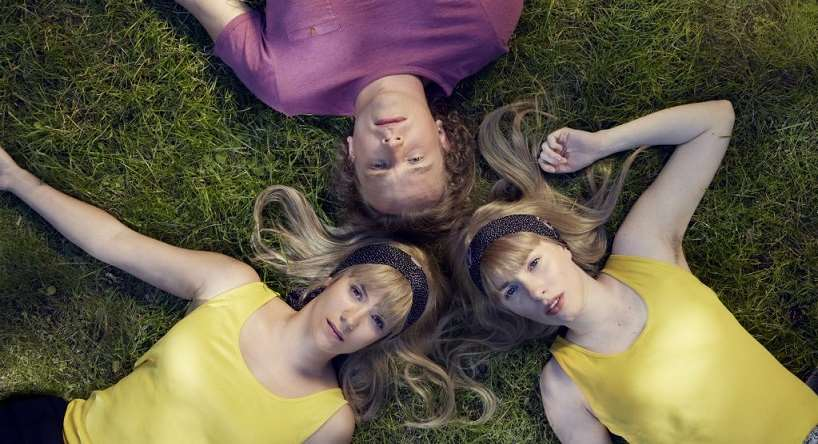 Två flickor och en pojke bildar en stjärna i gröngräset