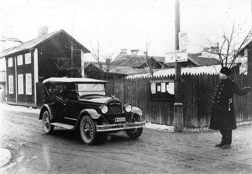 Svartvit bild från Gruvgatan med bil och poliskonstapel modell 1929.