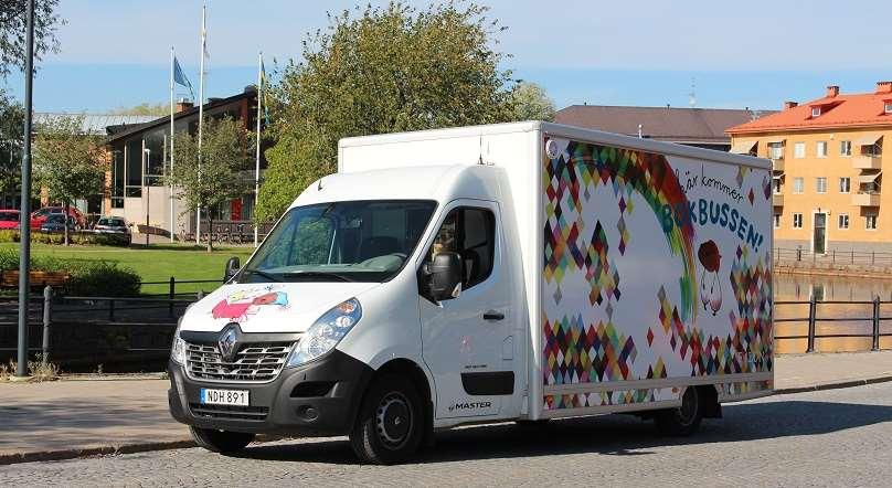 Färgbild av bokbussen snett framifrån körandes intill Faluån en sommardag.