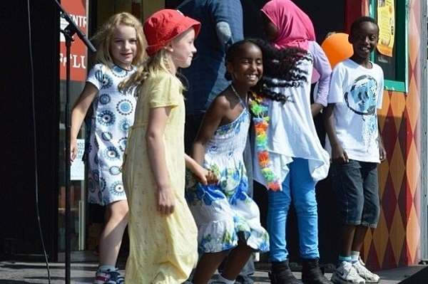 Glada barn dansar på en scen.