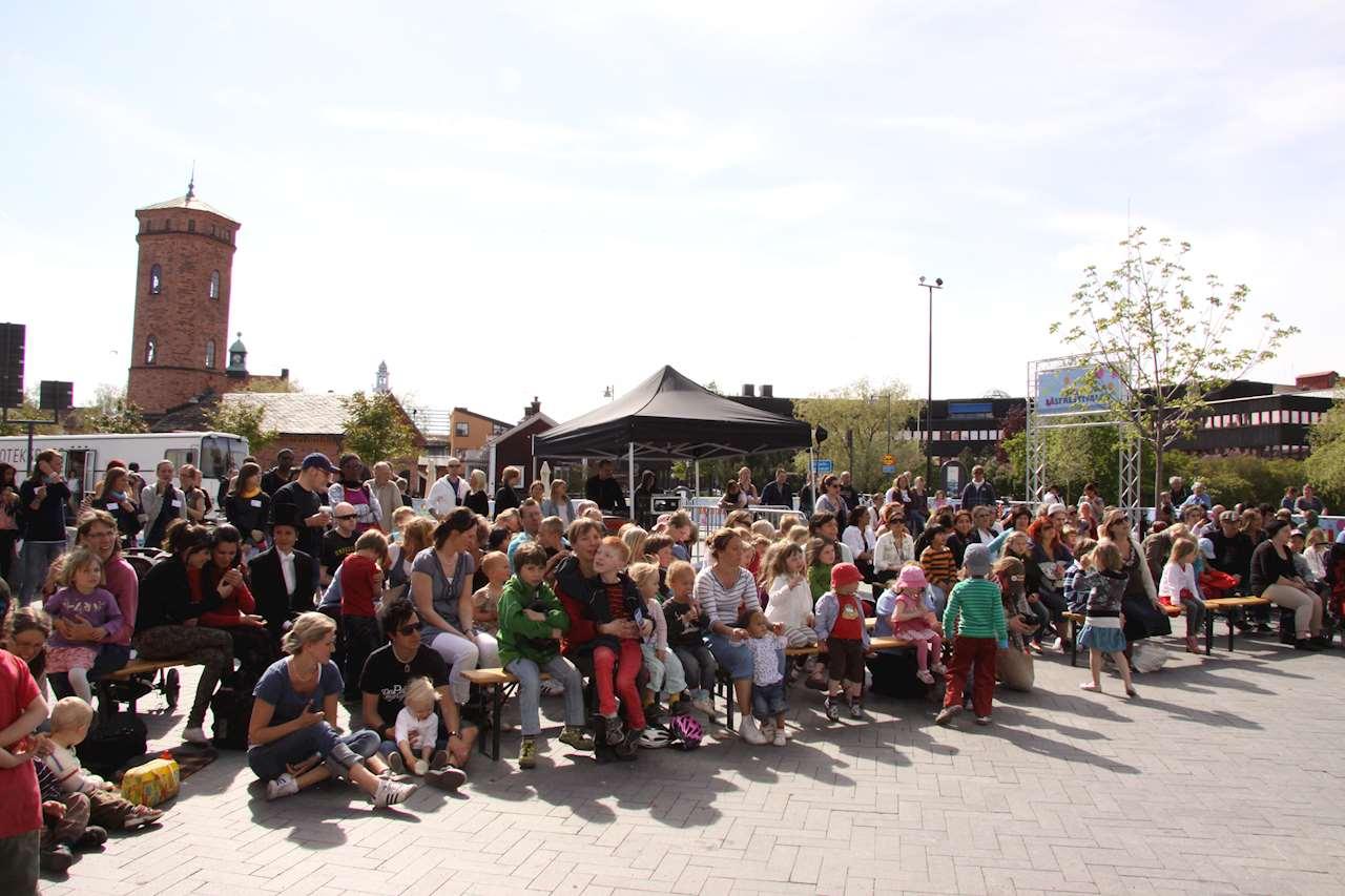 Folksamling med både barn och vuxna framför en scen utomhus.