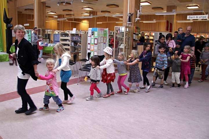 En vuxan leder ett långt led med barn genom biblioteket.