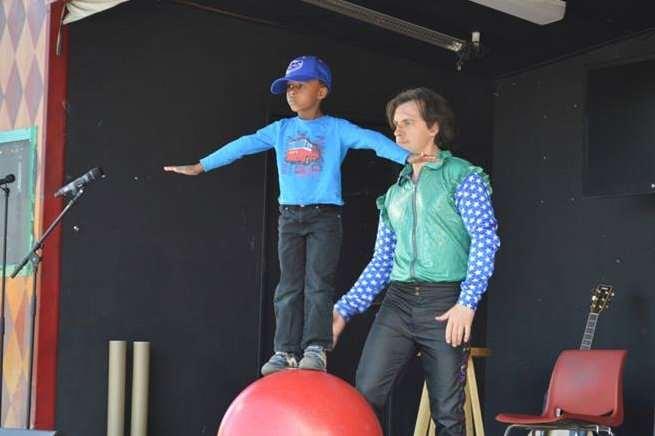 En pojke får hjälp att balansera på en jättestor röd boll uppe på en scen.