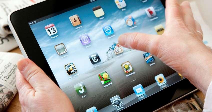 Händer som håller i och klickar på en iPad