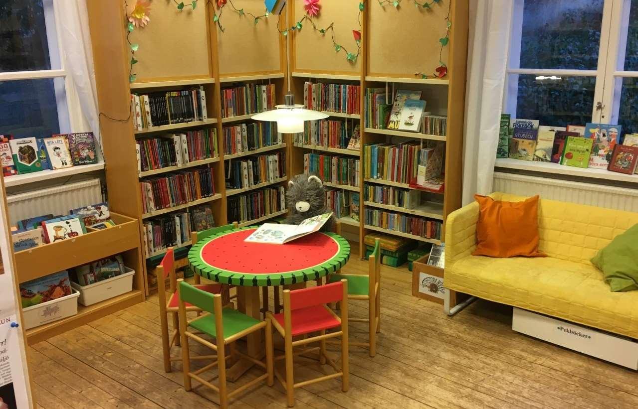 Interiör barnavdelningen Näs bibliotek: teddybjörn sitter och läser vid runt bord